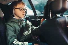 Boy watch a tablet on the car back seat Royalty Free Stock Images