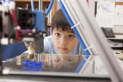 Boy watches machine intently. Royalty Free Stock Photos