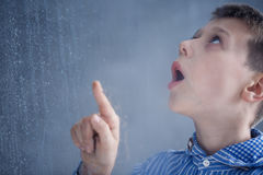 Boy watches rain Royalty Free Stock Photo