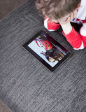 Boy watching cars movie on tablet pc Royalty Free Stock Photos