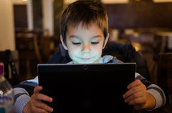 Boy with watching cartoons on tablet. Young boy watching cartoons on tablet in a restaurant stock photos