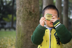 Boy watching through color filter. Chinese boy watching through color filter in park stock photos