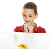 Boy Watching Dreidel Spin. Boy watching a Hanukkah dreidel spin, with chocolate gelt in the foreground.  Isolated on white Stock Images