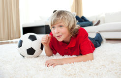 Boy watching football match lying on the floor Royalty Free Stock Photo