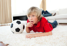 Boy watching football match lying on the floor Royalty Free Stock Image