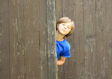 Boy watching from gate. Little kid - smiling boy in blue t-shirt watching from wooden gate Royalty Free Stock Photography