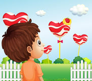 A boy watching the giant lollipops Stock Images