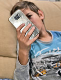 Boy watching his cell phone. Teenager connected to social networks Royalty Free Stock Photos