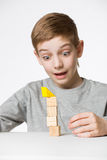 Boy watching house made of wooden blocks fall Stock Images