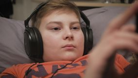 Boy watching media content using headphones and mobile phone app lying on the couch at home. Close Up of boy hands. Playing video games on cell phone in the stock video