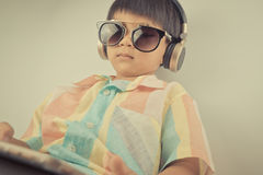 Boy is watching movie on headphone tablet Royalty Free Stock Image