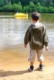 Boy watching pedalo in lake Stock Image