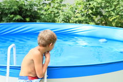 Boy watching a pool Royalty Free Stock Images