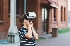 Boy watching simulation in virtual reality googles. Little child boy watching simulation in virtual reality googles Royalty Free Stock Photo
