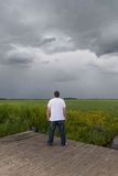 Boy watching the storm clouds. Young boy watching the gathering storm clouds over a green field Stock Images