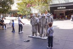 Boy watching street mime artist. Boy watching street mime or living statue artist in Melbourne Australia.  Only one of these statues is a man, the others are Royalty Free Stock Photography