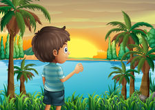 A boy watching the sunset at the riverbank Royalty Free Stock Image
