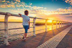 Boy watching sunset from St. Kilda Jetty. Melbourne, Victoria, Australia. Color toning effect Royalty Free Stock Photos
