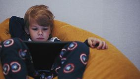 Boy watching tablet while sitting on a pouf stock footage