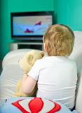 Boy watching TV. Baby boy watching cartoons in TV Royalty Free Stock Photo