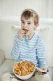Boy watching TV while eating wheel shape snack pellets Royalty Free Stock Image