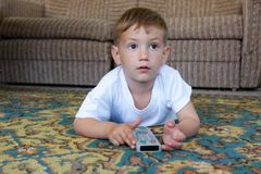 Boy watching tv at home. Cute boy watching tv at home Stock Photography