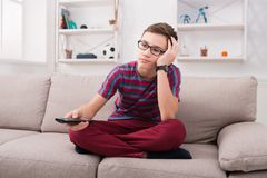 Boy watching tv and looking bored on couch at home. Boring movie. Teenager holding remote control and looking dull while sitting the couch at home in living room Royalty Free Stock Images