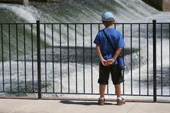 Boy Watching Water at Dam. Young boy watching water as it goes over dam. Horizontal format Stock Image