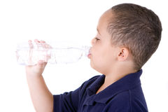 Boy with water bottle. Happy latino boy drinking from water bottle on white background Royalty Free Stock Photo