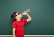 Boy with water bottle and school board Royalty Free Stock Photos