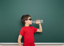 Boy with water bottle and school board Stock Photography