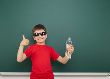 Boy with water bottle and school board Royalty Free Stock Photography