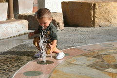 Boy & Water Fountain. Water sprays up from the ground at a young boy Royalty Free Stock Photo
