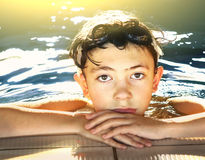 Boy in water galsses close up portrait in swimming pool. Teen preteen boy in swiming pool close up face portrait Royalty Free Stock Image