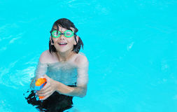 Boy with Water Gun. Smiling teenage boy in the pool pointing an orange water gun Royalty Free Stock Photo