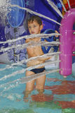 Boy in the water park splashes water jet Stock Photos