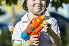 A boy and a water pistol Royalty Free Stock Image