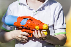 A boy and a water pistol. Boy playing in the street water pistol Stock Image