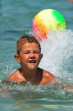 Boy in the water playing with a ball. In the sea Stock Image