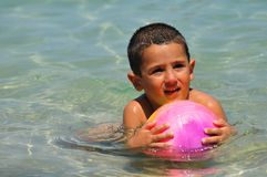 Boy in the water playing with a ball. In the sea Royalty Free Stock Images