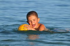 Boy in the water playing with a ball. In the sea Stock Photography