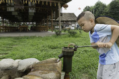 Boy at water pump Stock Photo