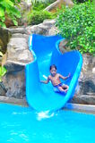 A boy on a water slide. A smiling boy enjoying a bouncy water  slide Stock Images