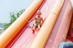 Boy on a water slide Royalty Free Stock Image