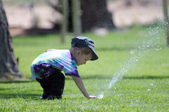 Boy at water sprinkler Royalty Free Stock Images