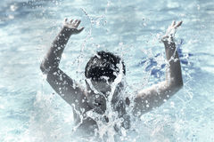 Boy in water summer splash. Young boy playing and splashing water in a pool during summertime Stock Image