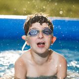 Boy in water with thumbs. Portrait of a boy in a pool Stock Photography