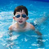 Boy in water with thumbs. Portrait of a boy in a pool Royalty Free Stock Images