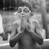 Boy in water with thumbs. Portrait of a boy in a pool, black and white Royalty Free Stock Photos