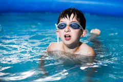 Boy in water with thumbs. Boy swimming in the pool Royalty Free Stock Photos